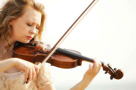 lover: Portrait of blonde girl music lover on beach playing the violin. Love of music concept.