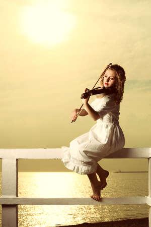Le m�lomane jeune fille blonde sur le quai avec un violon au coucher du soleil ou le lever du soleil. Amour du concept de musique.