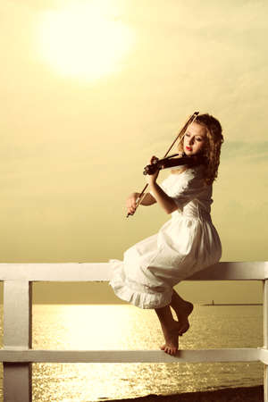 The blonde girl music lover on pier with a violin at sunset or sunrise.  Love of music concept. photo