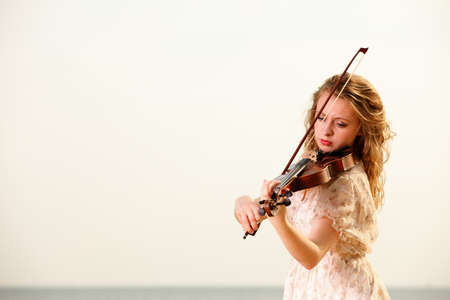 of mozart: The blonde girl music lover on beach playing the violin. Love of music concept.