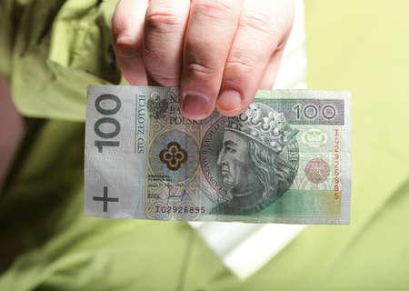 Businessman holding polish money hundred zloty banknote photo
