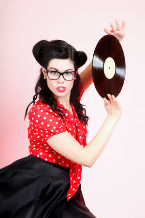 Sexy girl with phonography analogue record music lover pink background photo