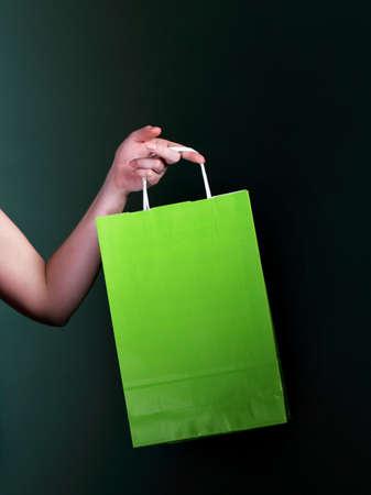mmc: Female hand holding green paper shopping bag on dark background Stock Photo