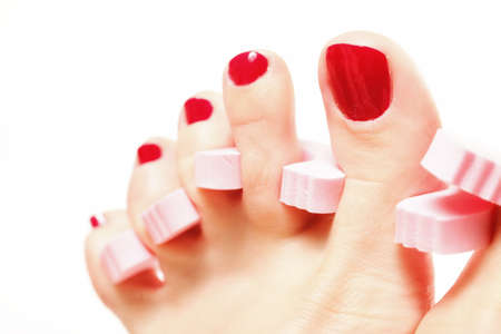 foot pedicure applying womans feet with red toenails in toe separators white background photo