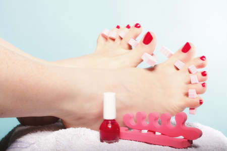 separators: foot pedicure applying womans feet with red toenails in pink toe separators blue background