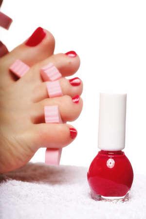 s�parateurs: p�dicure pied appliquer les pieds de la femme avec des ongles rouges dans s�parateurs d'orteils en arri�re-plan blanc