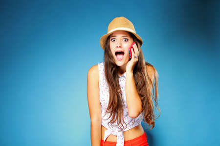 woman dialing phone number: Surprised shocked summer girl talking on mobile phone, blue background