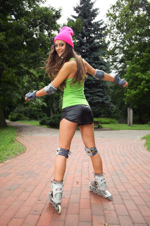 inline skates: Happy young girl enjoying roller skating rollerblading on inline skates sport in park. Woman in outdoor activities