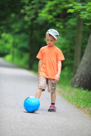 Boy young kid playing with ball kicks running towards ball in park outdoors photo