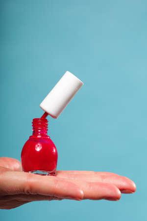 naildesign: Pedicure manicure red nail polish bottle on female hand blue background