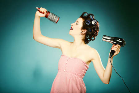 young woman preparing to party having fun, funny girl styling hair with curlers hairbrush and hairdreyer retro style blue background photo