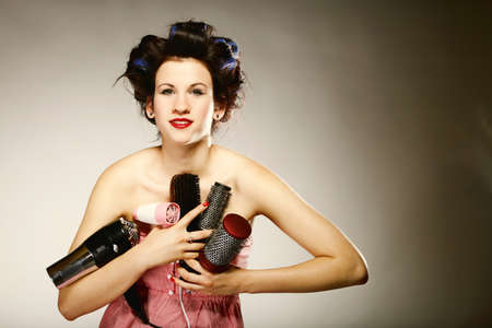 young woman preparing to party having fun, funny girl with curlers and many accessories for styling hair comb brushes hairdreyer retro style grey background Stock Photo - 20980738