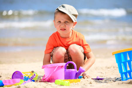Child in action little boy playing toys on beach sea background photo