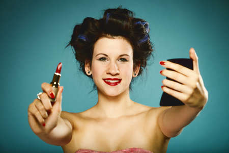 young woman preparing to party having fun, girl styling hair with curlers applying make red lipstick in hand up retro style blue background photo