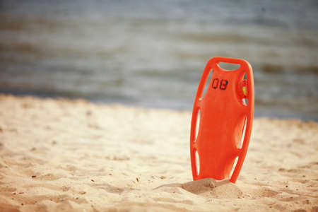 Beach life-saving. Lifeguard rescue equipment orange preserver tool, red plastic buoyancy aid in the sand Stock Photo - 21077528
