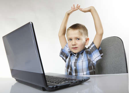 triumphing: Triumphing child boy with a laptop notebook computer on white background. Computer addiction.