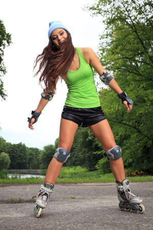rollerblading: Happy young girl enjoying roller skating rollerblading on inline skates sport in park. Woman in outdoor activities