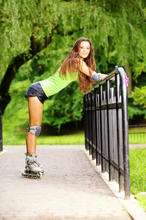 rollerblades: Happy young girl enjoying roller skating rollerblading on inline skates sport in park. Woman in outdoor activities