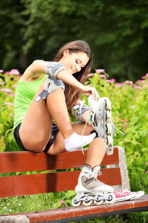 roller blade: Happy young girl enjoying roller skating rollerblading on inline skates sport in park. Woman in outdoor activities
