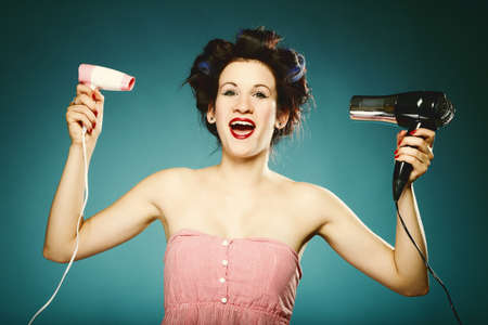 young woman preparing to party having fun, funny girl styling hair with curlers and hairdreyer retro style blue background photo