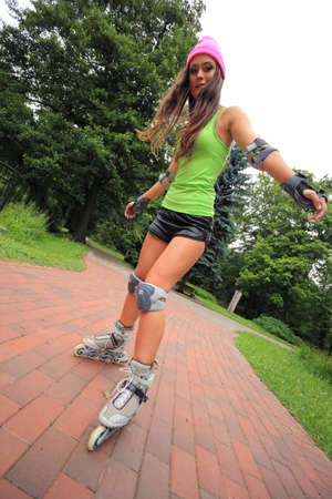 Happy young girl enjoying roller skating rollerblading on inline skates sport in park. Woman in outdoor activities photo