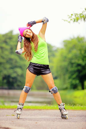 Happy young girl enjoying roller skating rollerblading on inline skates sport in park. Woman in outdoor activities Stock Photo - 21173960