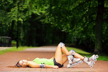 Happy young girl enjoying roller skating rollerblading on inline skates sport in park. Woman in outdoor activities Stock Photo - 21173965