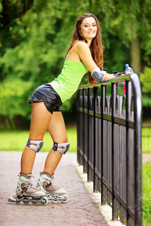 Happy young girl enjoying roller skating rollerblading on inline skates sport in park. Woman in outdoor activities Stock Photo - 21173968