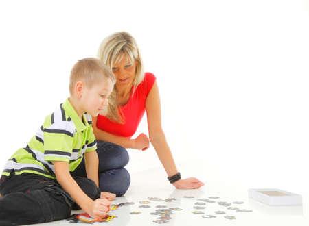 madre facendo gioco di puzzle giocattolo insieme con suo figlio sul pavimento isolato su sfondo bianco