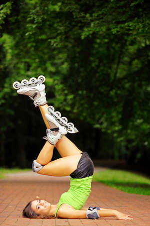 roller blade: Happy young girl enjoying roller skating rollerblading on inline skates sport in park. Woman in outdoor activities shoulder stand pose Stock Photo