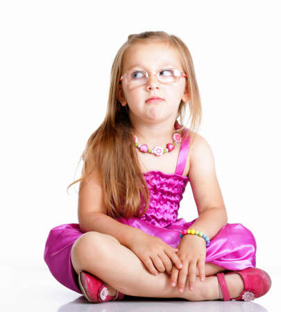 cute little girl glasses sitting on floor looking to the side studio shot isolated on white background photo
