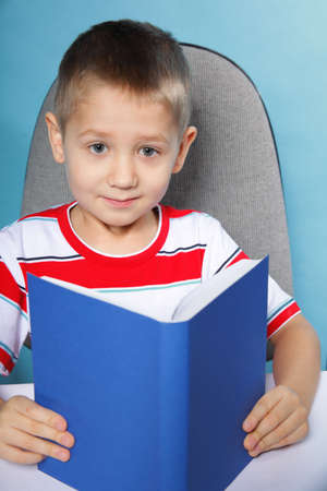 Young boy reading a book, child kid on blue background holding an open book photo