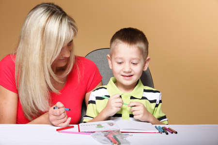 mother and son drawing together, mom helping with homework daycare brown background photo