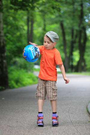 Boy in action young kid playing with ball in park outdoors. Healthy leisure time Stock Photo - 21272209