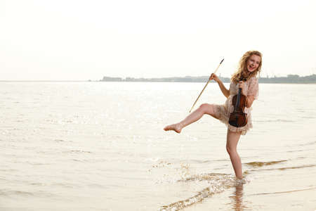 Happy crazy blonde girl music lover on beach with a violin. Love of music concept. photo