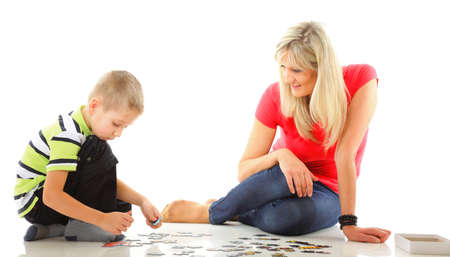 mother doing playing puzzle toy together with her son on floor isolated on white background photo
