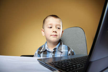 Computer addiction child boy with laptop notebook brown background photo