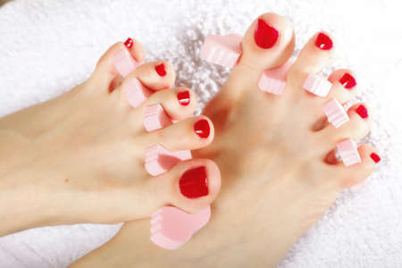 foot pedicure applying womans feet with red toenails in toe separators photo