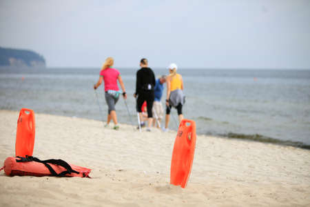 buoyancy: Beach life-saving. Lifeguard rescue equipment orange preserver tool, red plastic buoyancy aid in the sand