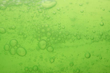 Green abstract blurred liquid background with soap bubbles photo