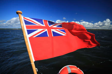 ensign:  The UK red ensign the british maritime flag flown from a yacht sail boat blue sky and sea