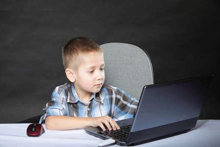 Computer addiction child boy with laptop notebook black background photo