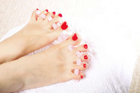 separators: foot pedicure applying womans feet with red toenails in toe separators Stock Photo