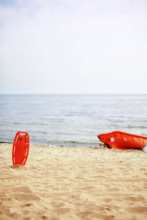 buoyancy: Beach life-saving. Lifeguard rescue equipment orange preserver tool and boat, red plastic buoyancy aid in the sand