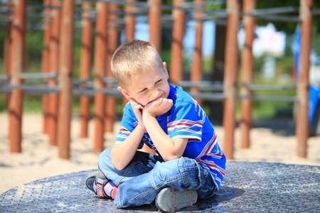 thoughtful child boy or kid in playground on leisure equipment photo