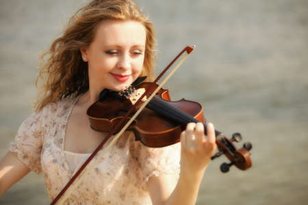 Portrait of blonde girl music lover on beach playing the violin. Love of music concept. photo