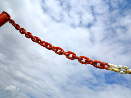 Old rusty metal steel red white chain links segment.  Sky cloudy background. photo