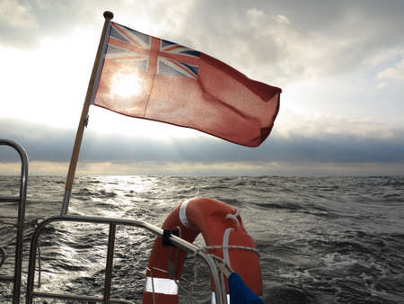 The UK red ensign the british maritime flag flown from yacht sail boat, stormy dark clouds sky and baltic sea. Summer and travel voyage photo