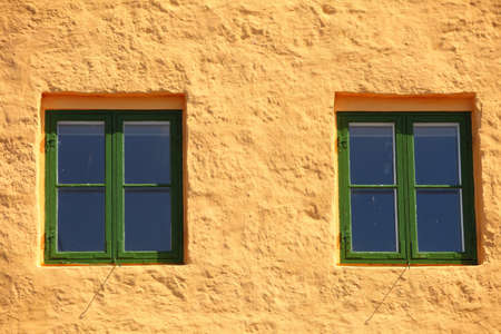 fasade: green two windows on orange wall background house fasade architecture detail, scandinavia Stock Photo