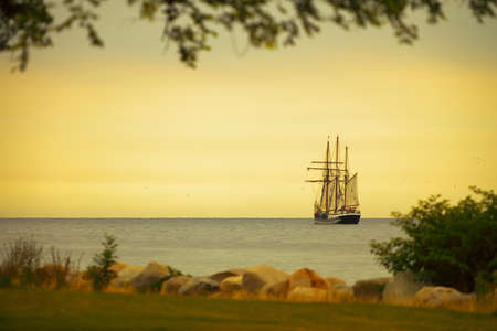 Beautiful tall sailing ship on sea at dusk sunset / sunrise photo